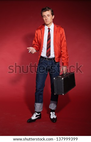 Retro fifties fashion man wearing red jacket and jeans. Holding a case and smoking.