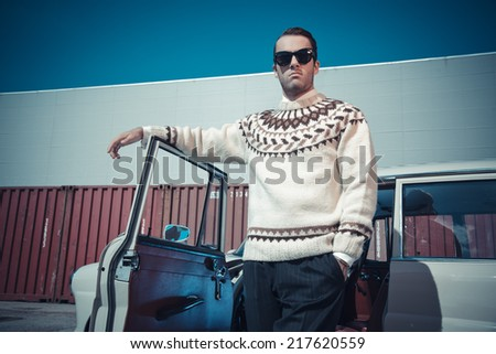 Retro fifties fashion man with woolen sweater and sunglasses standing against vintage car.