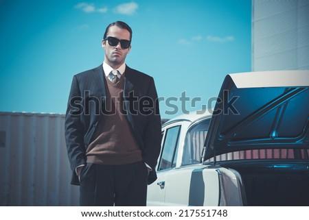 Retro fifties mafia fashion man standing next to open trunk of vintage car.