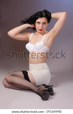 Retro fifties pin-up attractive girl in vintage bra and girdle and fishnet stockings on colorful background - pin-up concept