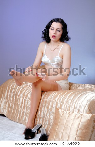 Retro fifties pin-up attractive girl in vintage satin bra and girdle in boudoir / bedroom - satin cover  pin-up concept