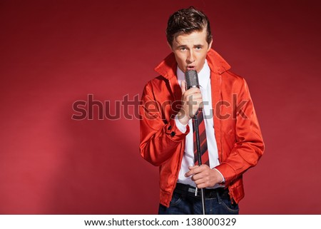 Retro fifties singer wearing red jacket with jeans and tie. Vintage microphone. ストックフォト ©