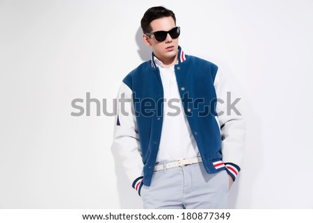 Retro fifties sportive fashion man wearing blue baseball jacket and dark sunglasses. Studio shot against white.