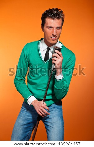Retro fifties style rock and roll singer with green shirt. Studio shot.