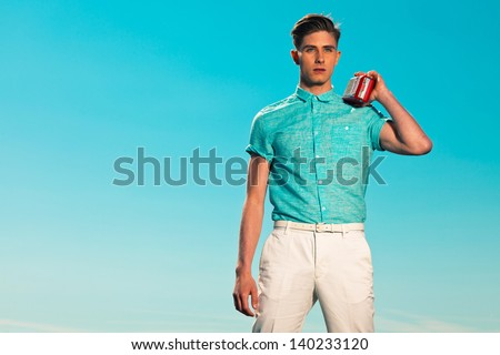 Retro fifties summer fashion man in blue shirt listens to portable radio. Outdoor. Blue sky.