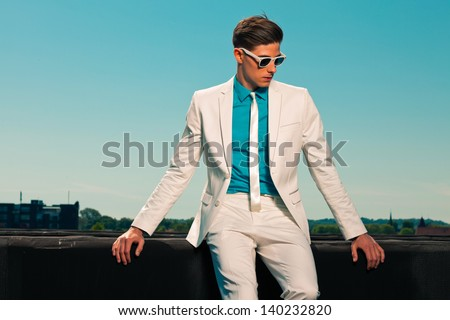 Retro fifties summer fashion man with white suit and sunglasses. On rooftop. Blue sky.