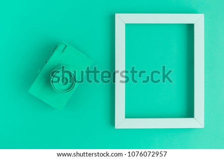 Retro film photo camera colored in turquoise with photo frame minimal abstract creative concept. Place for photo adding.