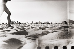 Retro film photo, vacation snapshot. Sunny day on the beach. Grain, blur, light leaks added as vintage effect.