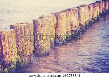 Retro filtered blurred abstract background made of wooden posts in water, shallow depth of field, space for text.
