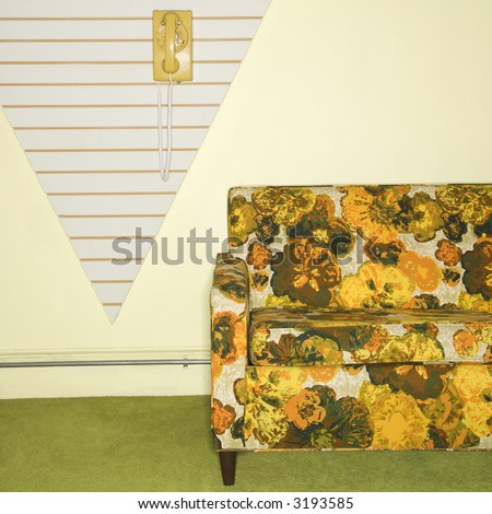 Retro floral printed sofa with yellow rotary phone hanging on wall.