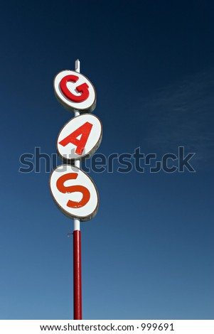 retro gas sign against blue sky - vertical version - stock photo