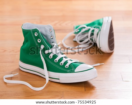 Retro green sneakers left on wooden floor