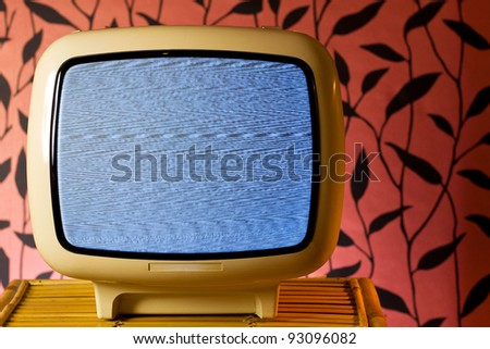 Retro grunge tv against wallpaper wall. White noise on television.