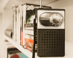 Retro handheld transistor radio on white shelf with cassettes and CDs in vintage colors vintage photography 2018