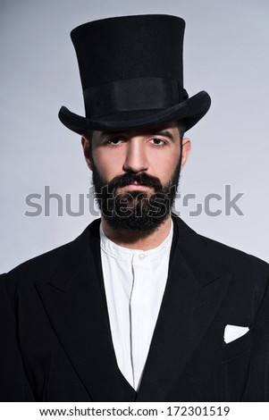 Retro hipster 1900 fashion man in suit with black hair and beard. Wearing black hat. Studio shot against grey.