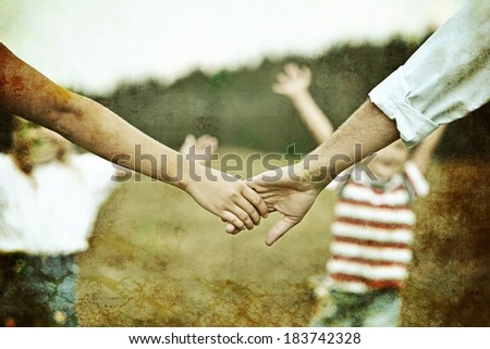 Retro image of a mother and father hands caring of children
