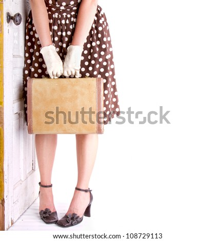 Retro image of a woman holding vintage luggage with a vintage door