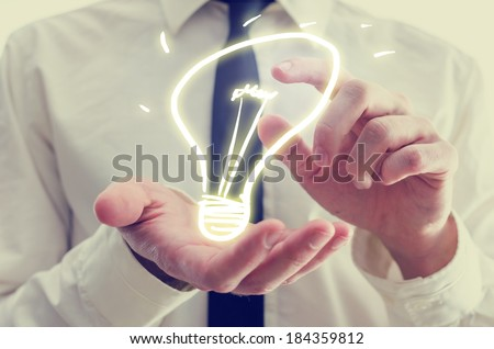 Retro image of businessman holding a creative light bulb icon in his hands conceptual of ideas, inspiration, imagination, and innovation.
