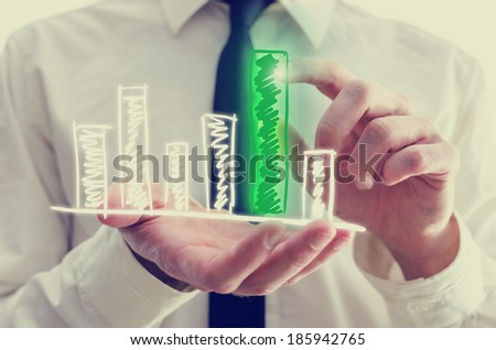 Retro image of businessman holding a hand-drawn bar graph in his hand with a single elevated green bar which he is touching and activating with his finger as though on a virtual computer interface.