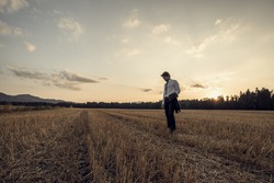 Retro image of businessman in elegant suit holding his jacket standing in mown wheat field under a majestic evening sky with a setting sun.