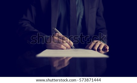 Retro image of businessman signing document or contract with silver pen on a black desk with reflection.