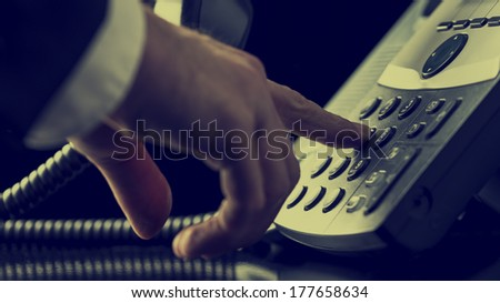 Retro image of man in a suit dialing out on a landline telephone with a close up view of his finger pressing a number button on the keypad as he makes a call. #177658634