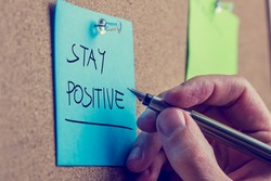 Retro instagram style image of a male hand writing Stay positive on blue post it paper pinned on cork bulletin board.