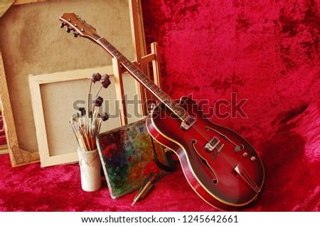 Retro jazz guitar, art easel, palette, brushes, picture frames
