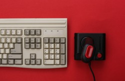 Retro joystick and old pc keyboard on red background. Gaming, video game competition. Top view