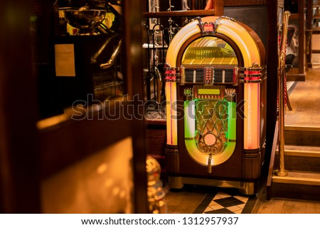 Retro jukebox in the corner of a restaurant by a set of stairs. #1312957937