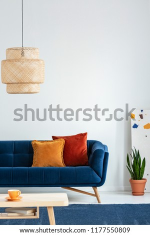Retro lampshade above a simple, wooden coffee table on a navy blue rug in a colorful living room interior with pillows on a couch. Real photo. #1177550809