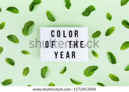 Retro lightbox with Color of the year wording and mint leaves random pattern on the trendy solid green backdrop, place for text