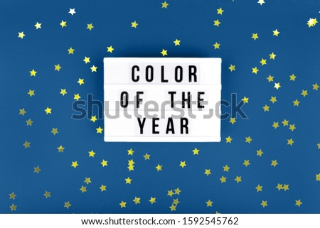 Retro lightbox with Color of the year wording on the trendy solid blue backdrop, place for text with festive golden star shaped confetti