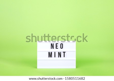 Retro lightbox with Neo Mint wording on the trendy solid bright green backdrop, place for text