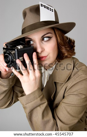 Retro looking woman holding a vintage camera.