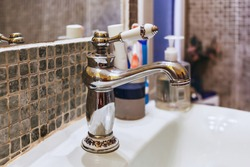 Retro metal faucet at wash basin, Interior of bathroom