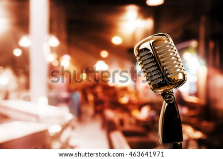 Retro microphone against blur colorful light in pub and restaurant background