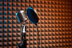 Retro microphone and pop filter for singing or recording a podcast on acoustic foam panel background, colorful light
