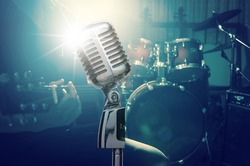 Retro microphone over the musician playing the guitar on band background with spot light, musical concept
