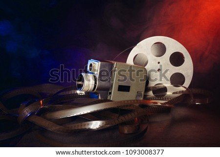 retro 8 mm movie camera with a reel of film in smoke. dark background