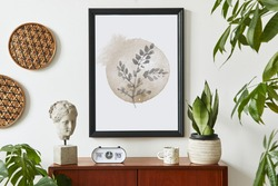 Retro modern compositon of living room interior with design teak commode, black mock up poster frame, clock, plant, decoration, white wall and personal accessories. Template.