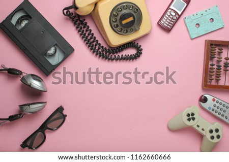 Retro objects on pink background. Rotary telephone, audio cassette, video cassette, gamepad, 3d glasses, tv remote, headphones, push-button phone. Analog media technology of  past. Copy space.