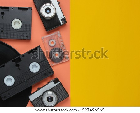 Retro objects. Retro camera, vinyl record, video cassettes, audio cassette on a colored background with copy space. 80s. Top view #1527496565