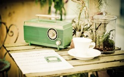 Retro of old radio with cup of coffee on wooden table.soft focus.