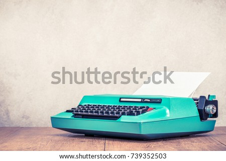 Retro old aged mint green typewriter circa 70s with paper blank on wooden table front concrete wall background. Vintage style filtered photo