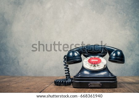 Retro old black rotary telephone on table front textured concrete wall background. Vintage style filtered photo #668361940