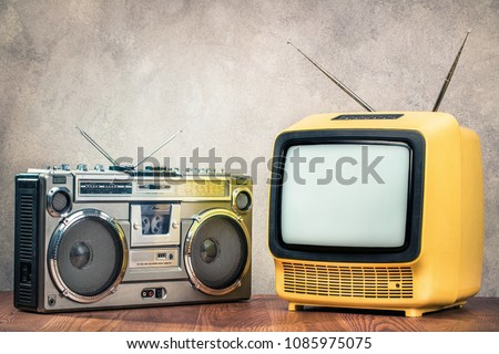 Retro old designed tube TV receiver and ghetto blaster stereo radio cassette tape recorder boombox from circa late 70s front concrete wall background. Vintage nostalgia style filtered photo