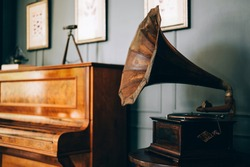 Retro old gramophone radio with horn speaker stands with old piano, Music and nostalgia concept. Vintage style.