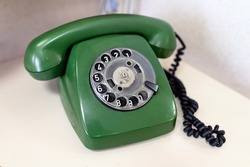 Retro old green phone with plastic dial pad with handset receiver