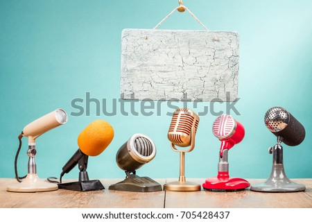 Retro old microphones for press conference or interview on table and hanging ?raquelure texture aged signboard blank front gradient aquamarine background. Vintage old style filtered photo
